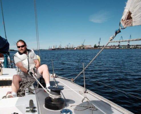 Mann hisst die Segel eines Segelschiffs