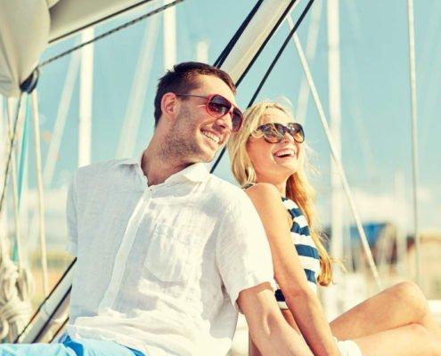 Pärchen sitzt happy auf einem Segelschiff