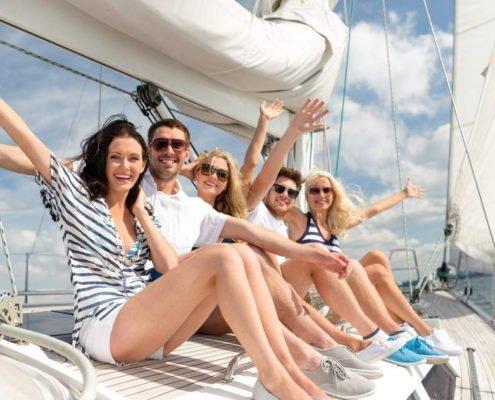 5 junge Leute sitzen auf einem Segelschiff